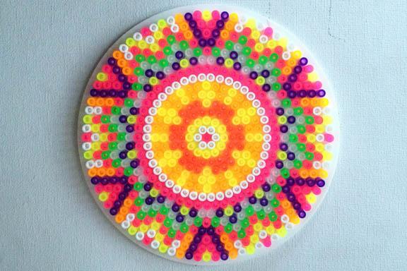 Neonfarvet perleplade Mandala. Formet som en sol - der blev til en blomst. Fotograf: Susanne Randers