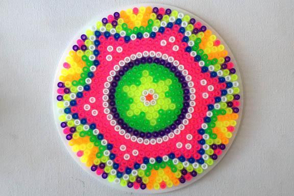 Neonfarvet perleplade Mandala. Formet som en stjerne. Fotograf: Susanne Randers