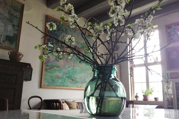 En smuk grønblå vase med friske grene fra haven pryder bordet midt i atelieret. Fotograf: Susanne Randers