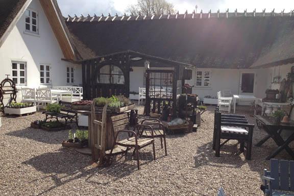 Nygårdens Gårdbutik i Nykøbing Sjælland. Gårdhave med borde og stole. Fotograf: Susanne Randers