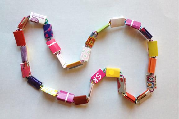 Farverig halskæde af go-cards og clips. Perfekt i længden til en barnehals. I frække røde, lilla, pink, gule og orange farver. 65 cm. 150 kr. Fotograf: Susanne Randers