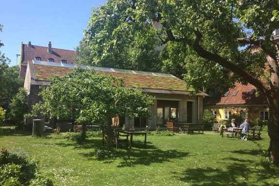 Grøn oase med fælleshus i midten. Fælleshuset rummer både udekøkken, gildesal og keramikværksted. Fotograf: Susanne Randers
