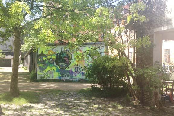 Fantastisk streetart graffiti væg. I god kontrast til gårdens romantiske look. Fotograf: Susanne Randers