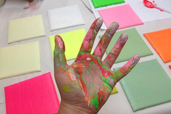 Skønt med maling på fingrene - og 15x15 lærreder i alle regnbuens farver. Fotograf: Susanne Randers