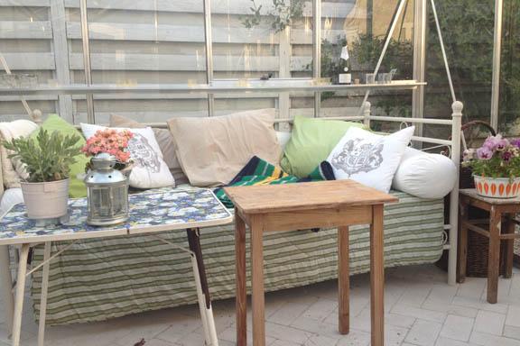 Jernsengen i mit drivhus - med puder og tæpper. Ren zen for sjælen. Fotograf: Susanne Randers