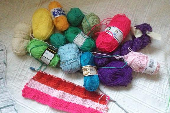 Yarnbombing regnbuefarvet strikketøj i gang til gårdens træer. Fotograf: Susanne Randers