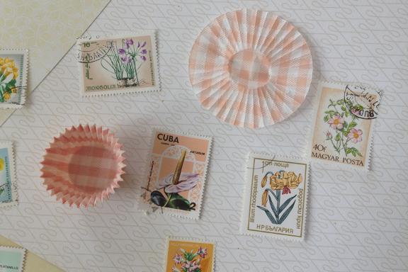 Moodboard til bordkort til fødselsdag. Her med frimærker og muffinsforme som små sole. Fotograf: Susanne Randers