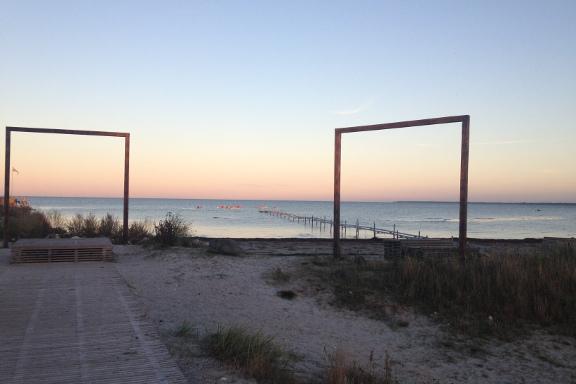 De opstillede rammer på strandengen skaber det smukkeste stilleben. Kajakroere i vandet nyder aftensolen. Fotograf: Susanne Randers